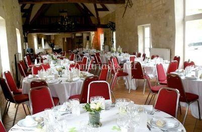 Nappes blanches et chaises rouges s'accordent à merveille avec les murs de pierres