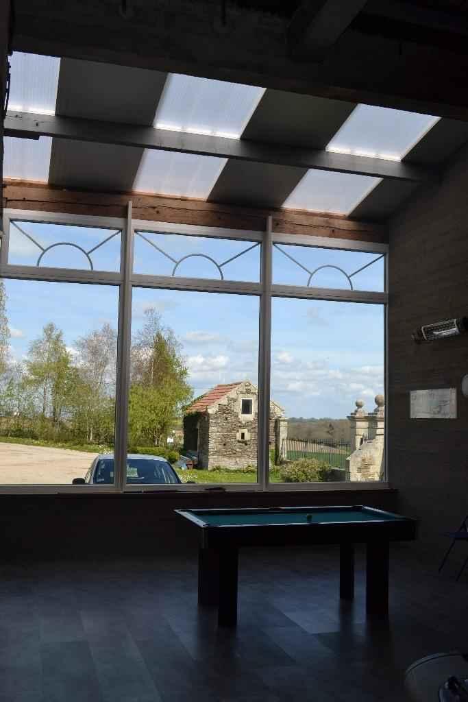 Grande baie vitrée donnant sur l'entrée du domaine