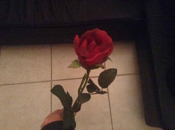 une rose rouge artificielle qui fait référence au bouquet des roses rouges du roi dans le Chateau de