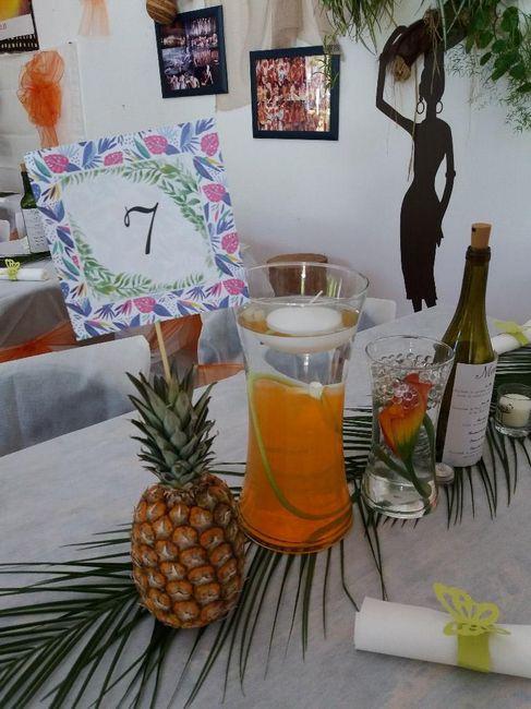 Ananas avec le numéro de table piqué dedans. Vase avec fleur immergée et bougie flottante dessus